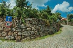 Gränden med stenväggen och VIKT BEGRÄNSAR FRAMÅT trafiktecknet arkivfoton