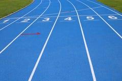 gränder av ett blått idrotts- spår med nummer ett två tre fyra f Arkivfoton