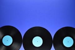 Gräns av gamla svarta vinylrekord på blå bakgrund Royaltyfria Bilder