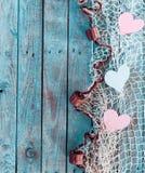 Gräns av romantiska hjärtor i fisknät Arkivfoto