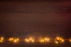 Gräns för girland för julljus över mörk träbakgrund Lekmanna- lägenhet, kopieringsutrymme royaltyfria bilder
