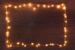 Gräns för girland för julljus över mörk träbakgrund Lekmanna- lägenhet, kopieringsutrymme arkivbild