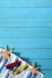 Gräns för sommarstrandbakgrund, solglasögon, handduk, sjöstjärna, blått wood kopieringsutrymme, lodlinje Royaltyfri Bild