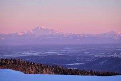 Gräns mellan Förenta staterna och Kanada Korkat berg för snö på solnedgången royaltyfri bild