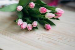 Gräns - rosa tulpanlögn på en trätabell Blommor som en gåva Arkivbilder