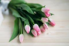 Gräns - rosa tulpanlögn på en trätabell Blommor som en gåva Arkivfoton