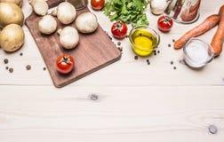 Gränsar förlägger vegetarisk mat för matlagning, nya champinjoner, morötter och olje- potatisar för persilja, för textträlantlig  royaltyfri fotografi