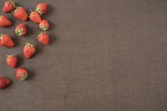 Gränsen av hela nya mogna röda jordgubbar som är ordnade på texturerade vänstra sidor på ett mörker, kritiserar bakgrund med copy arkivfoto