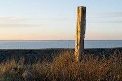 Gränsmärkepol på sjösidan i solnedgången Arkivbild