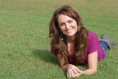 gräs som lägger den le kvinnan royaltyfri foto
