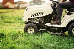 gräsklippningsmaskin som gör landskap arbeten och klippgräs Yrkesmässig arbetare som mejar gräsmatta Royaltyfria Foton