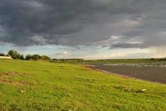 Gräsmatta längs sjön som ska kopplas av Och en mörk molnig himmel Royaltyfri Bild