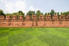 Gräsmatta- och tegelstenvägg Arkivfoton