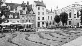 Gräsmatta och utomhus- för kafé hus nära i den gamla Riga staden Arkivfoton