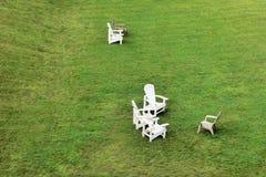 Gräsmattastolar som väntar på gäster på en stor vidd av gräsmatta royaltyfri foto