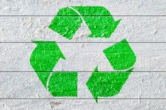Gräsplan återanvänder symbolet som målas på ett vitt naturligt texturerat trä Arkivfoto
