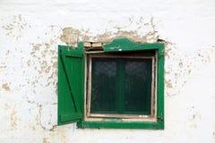 Gräsplan brutet träfönster på den skrapade vita väggen av det traditionella serbiska gyttjahuset som överges nu Arkivfoton