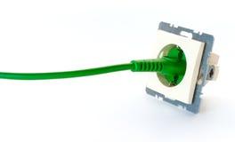 Gräsplan driver kabel som pluggas in i vägguttag without, täcker royaltyfri bild