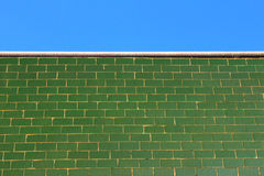Gräsplan glasade tegelplattaväggen och den blåa himlen Arkivfoto