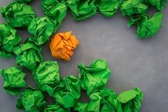 Gräsplan och apelsin crumped pappersbollar på läderbakgrund jpg Arkivfoto