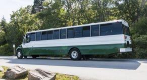 Gräsplan och vit turnerar bussen som parkeras på Acadianationalparken Arkivfoto