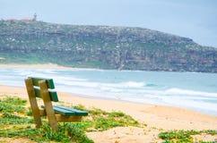 Gräsplan parkerar bänken nära havet, på Palm Beach, nordliga Sydney, Australien med det Barrenjoey nationalparkberget Arkivfoto