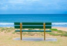 Gräsplan parkerar bänken nära havet, strandshowmörker - det blåa havet och horisonten fördunklar himmeldagen på Palm Beach, nordl Royaltyfria Foton