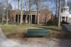 Gräsplan parkerar bänken på högskolauniversitetsområde Royaltyfri Bild