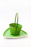 Gräsplan vävd korg och dekorativ grön platta Arkivfoto