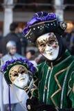 Gräsplanen och den purpurfärgade le maskeringen på den Venedig karnevalet Royaltyfri Bild