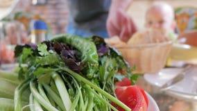 Gräsplaner och tomaten ligger på en platta i en restaurang Mot bakgrunden av behandla som ett barn äter och talar med föräldrar stock video