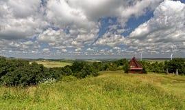 Gräsplanfält med väderkvarnar och ett trähus strukturerar sett in - between arkivbild