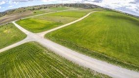 Gräsplanfält och lantlig väg på vår arkivbild