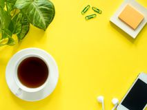 Gräsplansidor planterar kaffekoppen på det gula skrivbordet, den lekmanna- lägenheten, kopieringsutrymme Arkivbild