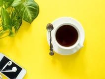 Gräsplansidor planterar kaffekoppen på det gula skrivbordet, den lekmanna- lägenheten, kopieringsutrymme Royaltyfri Fotografi