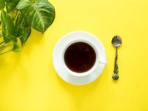 Gräsplansidor planterar kaffekoppen på det gula skrivbordet, den lekmanna- lägenheten, kopieringsutrymme Arkivfoto