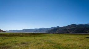 Grässlätt med bergbakgrund Royaltyfri Fotografi