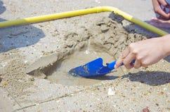 Gräva sanden i quadraten Arkivbilder