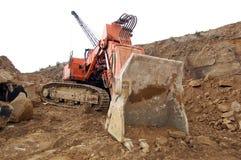 Grävare på ett stenvillebråd Arkivfoto