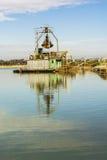 Grävare som muddrar i vattnet för grusgrop Arkivfoton