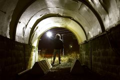 Grävaren med lyktan i den mörka tunnelen vände på - Diggery i ett övergett industriellt rum Royaltyfria Bilder