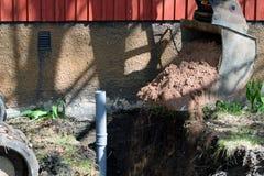 Grävskopa i konstruktionsplatsen som fyller diket för avklopprör med sand royaltyfri bild