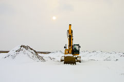 Grävskopa i Snow fotografering för bildbyråer