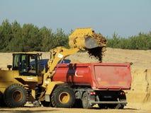 Grävskopa Loading The Transporter med sand royaltyfria bilder