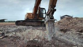 Grävskopa med den hydrauliska hammaredrillborren på arbete som ner bryter jord för konstruktion arkivfilmer