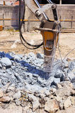 Grävskopa med den hydrauliska hammaren som bryter betong Arkivbild