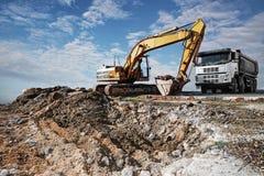 Grävskopa och lastbil på en konstruktionsplats Royaltyfri Bild