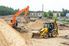 Grävskopa och traktor på konstruktionsplatsen royaltyfri fotografi