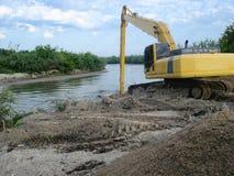 Grävskopa på floden royaltyfri foto