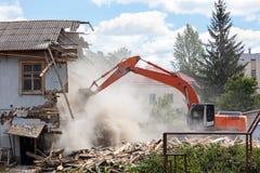 Grävskopa som arbetar på rivningen av en gammal bostads- buildi arkivbilder